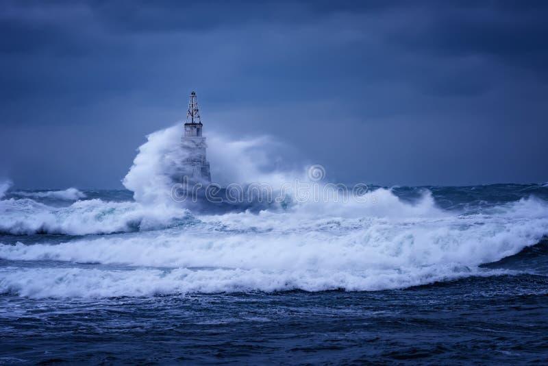 反对老灯塔的大波浪在阿赫托波尔,黑海,保加利亚港在一喜怒无常的风暴日 危险,剧烈的场面 库存图片