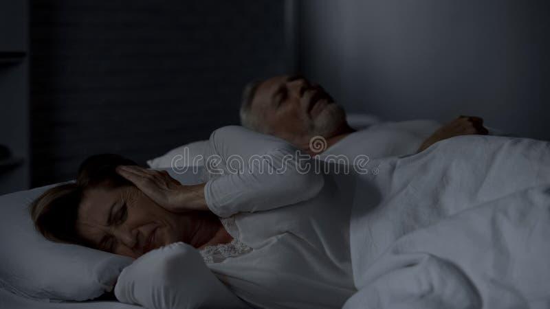 反对耳朵的年长女性紧迫的手倾斜睡眠,打鼾在床上的人 免版税库存照片