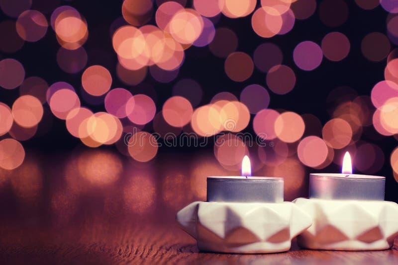 反对背景的两个蜡烛与Bokeh 库存照片