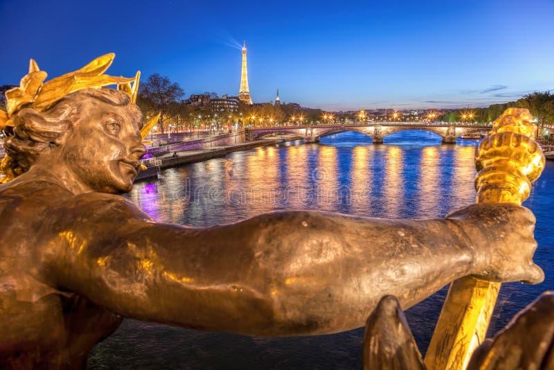反对艾菲尔铁塔的亚历山大III桥梁在晚上在巴黎,法国 免版税库存照片