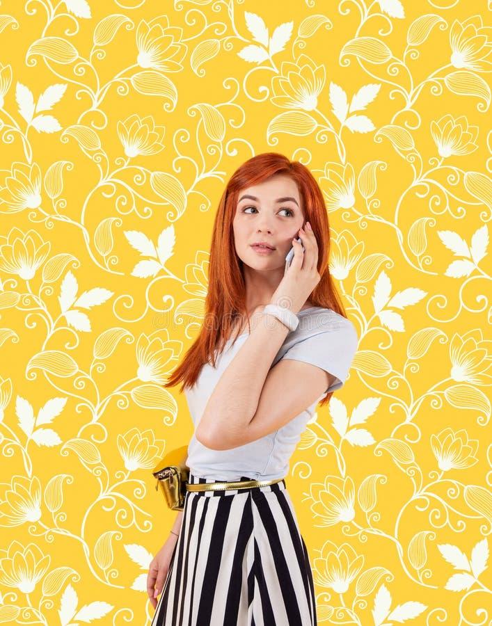 反对花背景的美女身分和谈话在电话 库存照片
