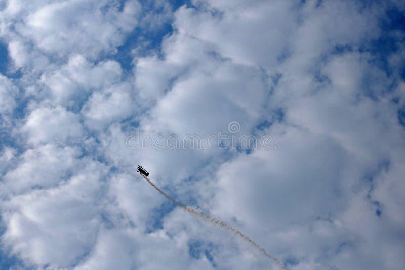 反对落后烟的云彩的双翼飞机显示 库存图片