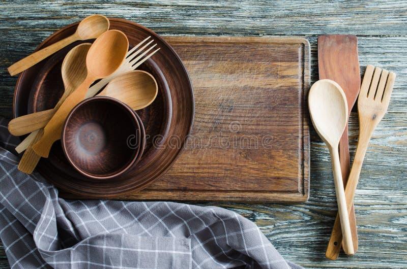 反对葡萄酒木背景的简单的土气厨具 库存照片