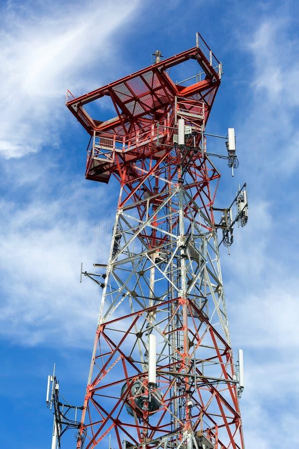 反对蓝天和白色云彩的手机多孔的塔 免版税图库摄影