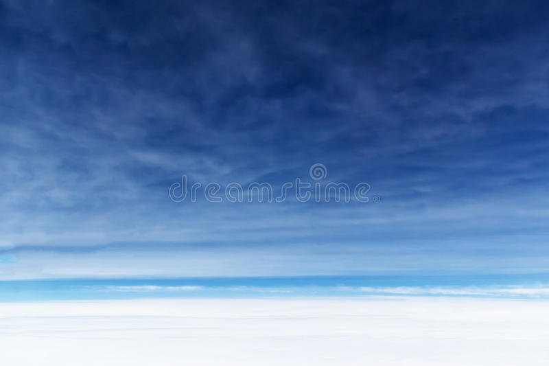 反对蓝天的意想不到的软的白色云彩在雨云下 免版税库存照片