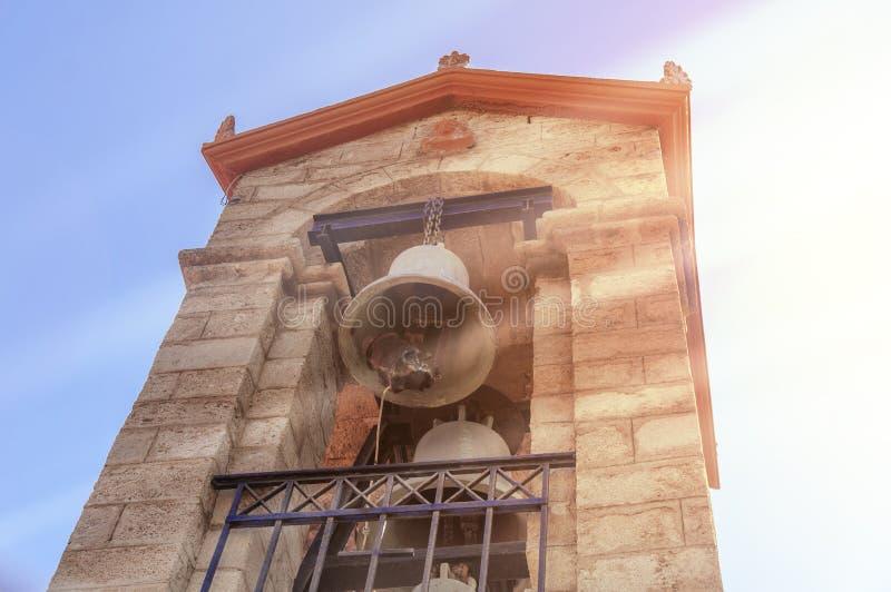 反对蓝天的教堂钟塔与太阳火光在希腊海岛 免版税库存照片