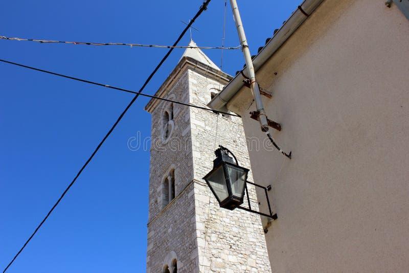 反对蓝天的新生钟楼与在墙壁上的灯笼 库存照片