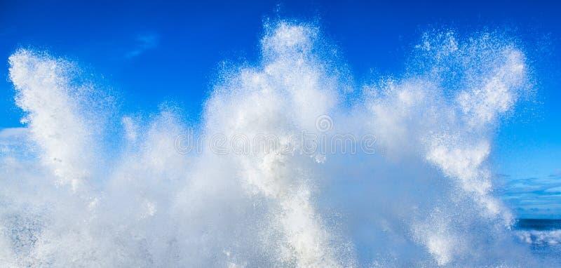 反对蓝天的新鲜的干净的浪端的白色泡沫海浪 图库摄影