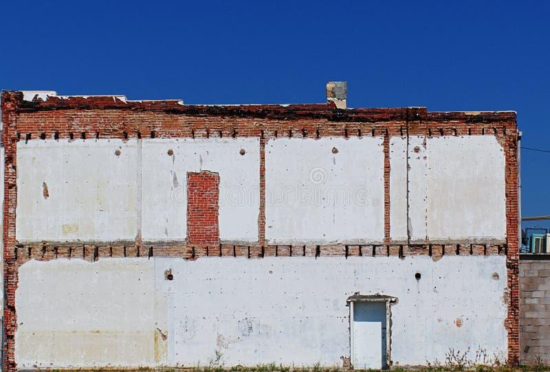 反对蓝天的白色和红砖墙壁 免版税库存图片