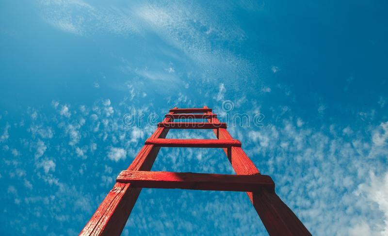 反对蓝天的红色楼梯休息,正面图 发展刺激事业成长概念 免版税库存照片