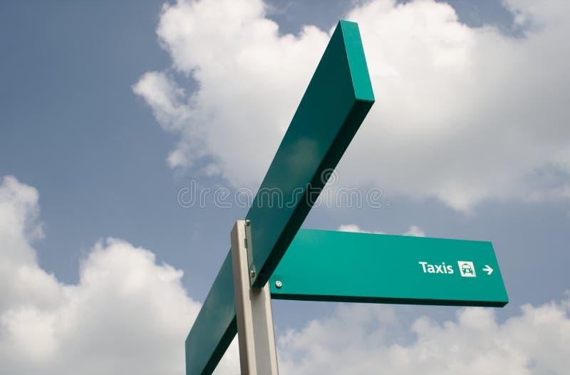反对蓝天的绿色出租汽车标志与云彩 空间到文本的左边 免版税库存图片