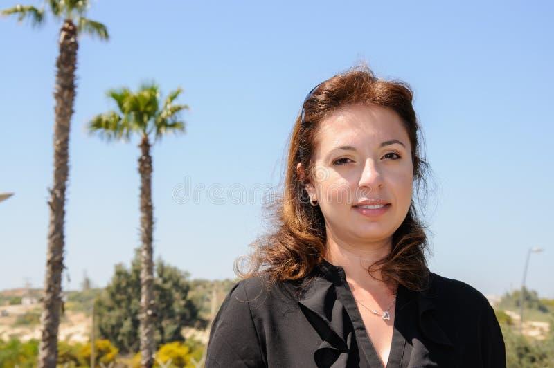 反对蓝天的美丽的年轻中东妇女画象 免版税图库摄影