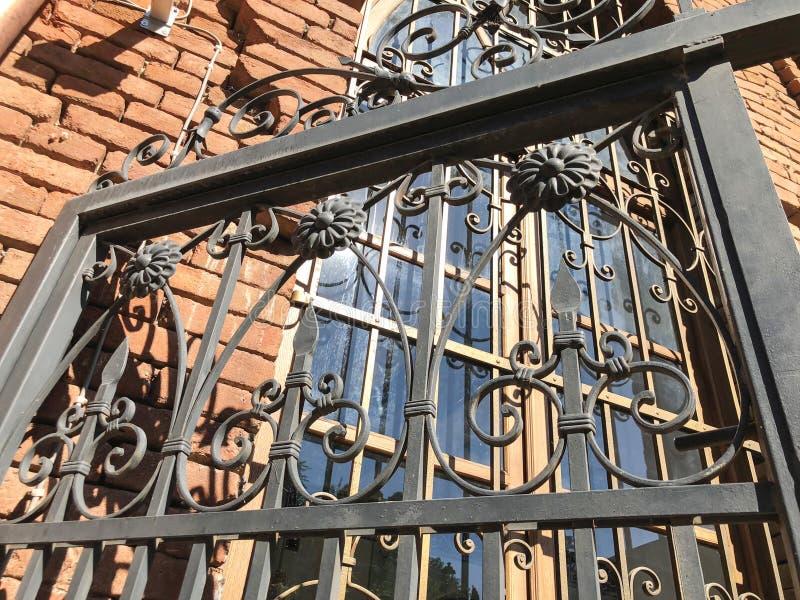 反对蓝天的美好的铁门 老第比利斯建筑学 窗口和外部装饰在夏日 免版税库存图片