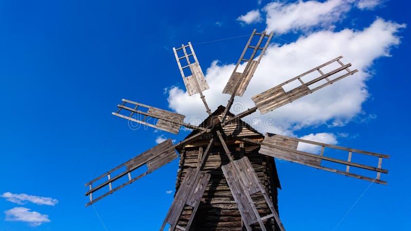 反对蓝天的老和残破的木风车 免版税库存照片