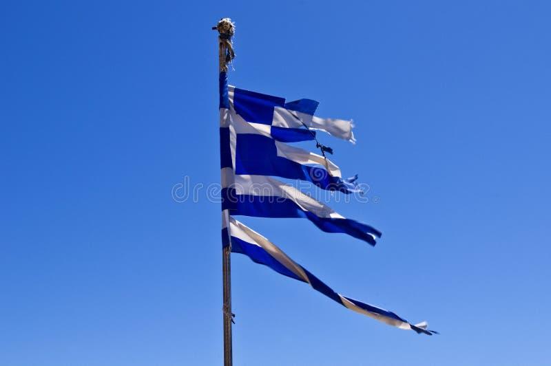 反对蓝天的被撕毁的希腊旗子 免版税库存图片