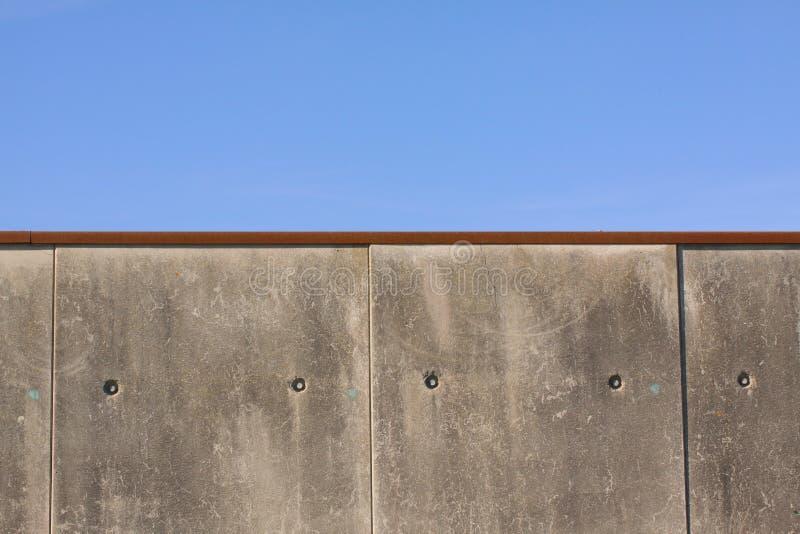 反对蓝天的边界或监狱水泥灰色混凝土墙-接近与拷贝空间 免版税库存图片