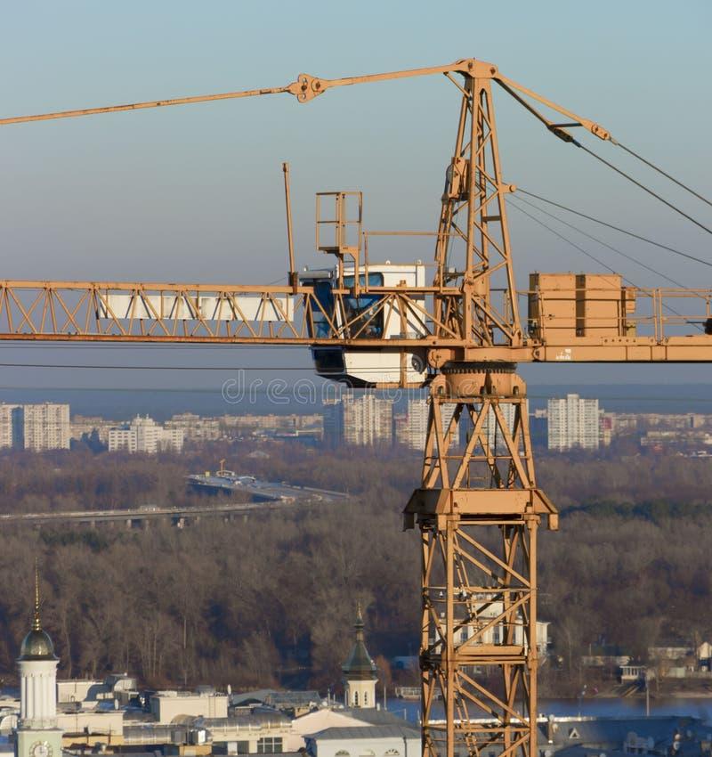 反对蓝天的黄色工业建筑用起重机 免版税图库摄影