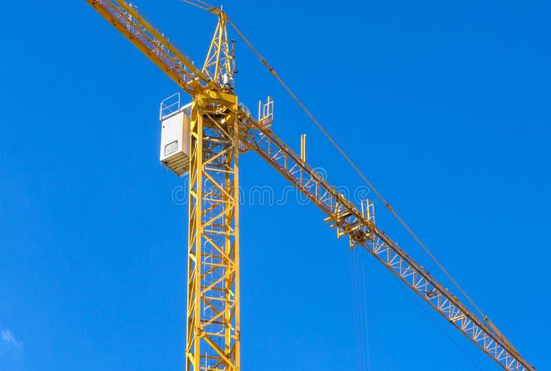 反对蓝天的黄色建筑塔吊 免版税库存图片