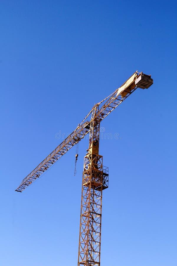 反对蓝天的黄色建筑塔吊 免版税图库摄影