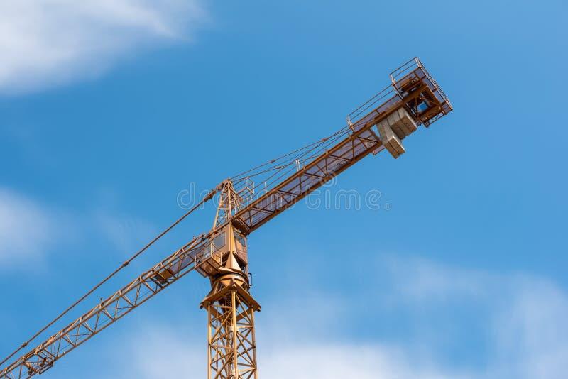 反对蓝天的黄色建筑用起重机与白色云彩 库存图片