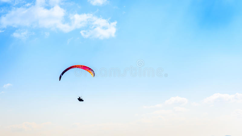 反对蓝天的滑翔伞飞行与白色云彩 库存图片