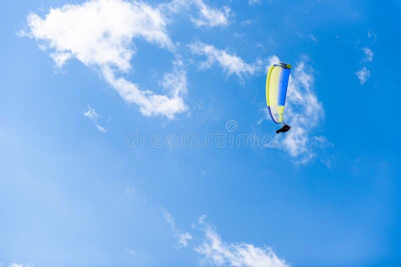 反对蓝天的滑翔伞飞行与白色云彩 免版税图库摄影