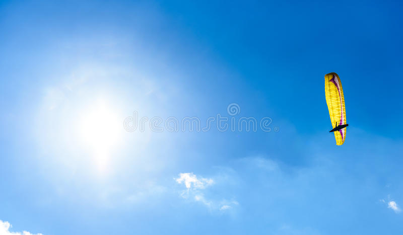 反对蓝天的滑翔伞飞行与白色云彩 免版税库存照片