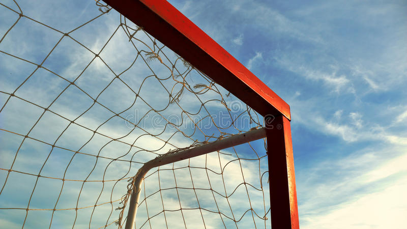 反对蓝天背景的红色足球目标 免版税库存图片
