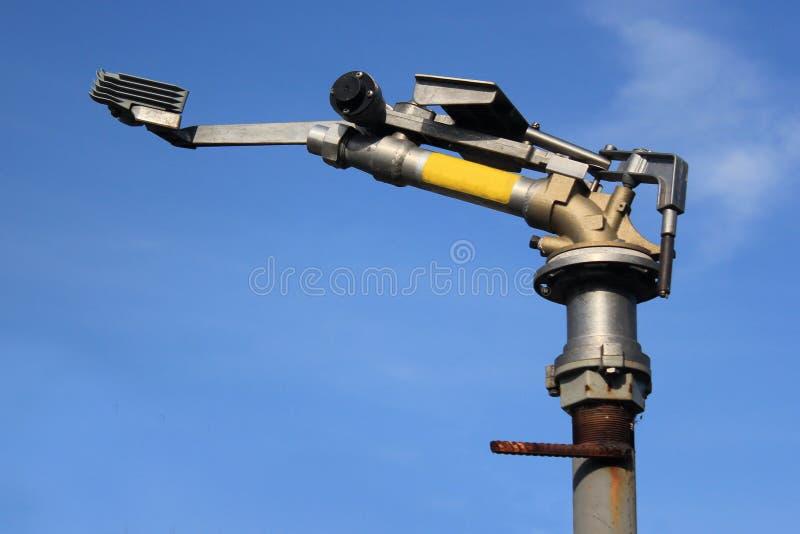 反对蓝天背景的转动的水喷洒的大炮 库存照片