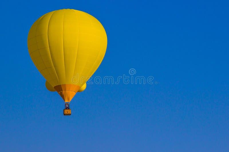 反对蓝天背景的黄色热空气气球 免版税图库摄影