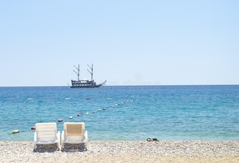 反对蓝天,天蓝色的水,黄沙和老海船的两张海滩睡椅在天际 背景海滩蓝色五颜六色的天空伞假期 免版税库存照片
