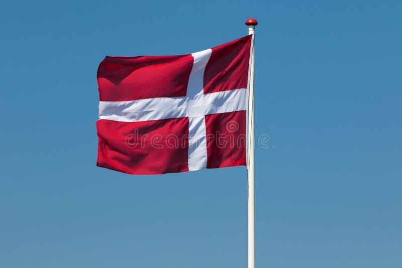 反对蓝色夏天天空的丹麦旗子 免版税图库摄影