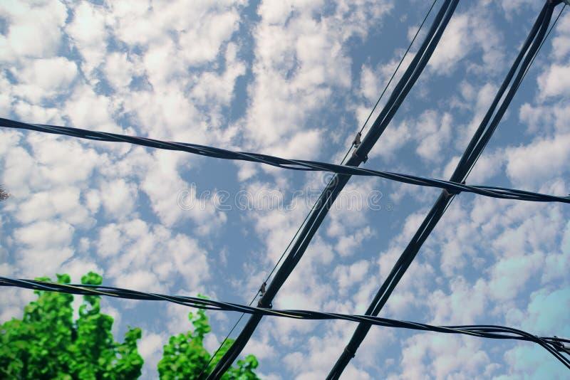 反对蓝色多云天空的两条相交的线导线 免版税库存照片
