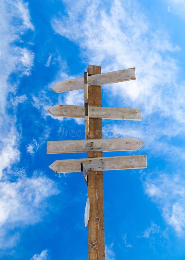 反对蓝色多云天空的老木箭头路标 免版税库存图片