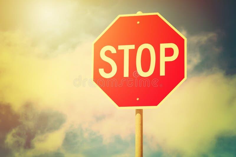 反对蓝色多云天空背景的红色停车牌 交通管理警报信号 定调子 免版税库存图片