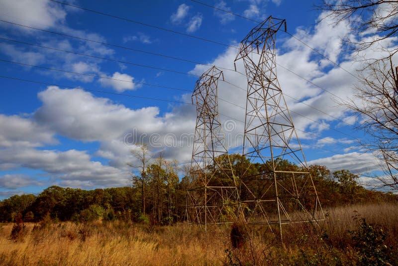 反对蓝色明亮的天空的输电线 库存图片