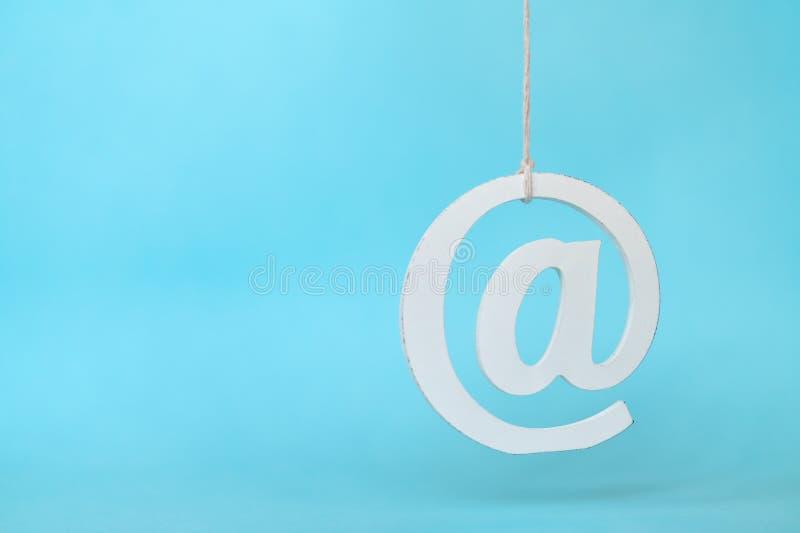 反对蓝色背景的垂悬的电子邮件象 库存照片