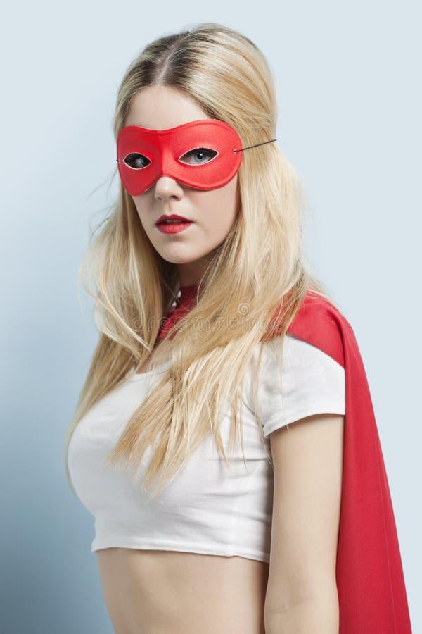 反对蓝色背景的少妇佩带的超级英雄服装画象  免版税库存照片