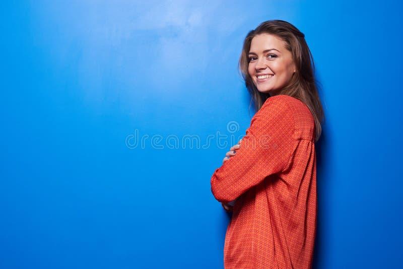 反对蓝色背景的兴奋的年轻女性身分 免版税库存照片