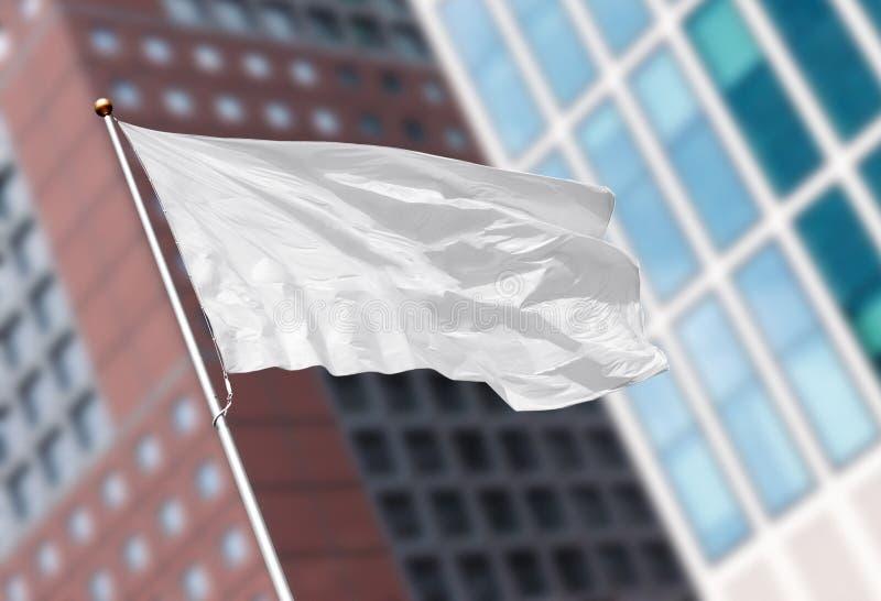 反对被弄脏的现代大厦的白色空白的旗子 免版税库存照片