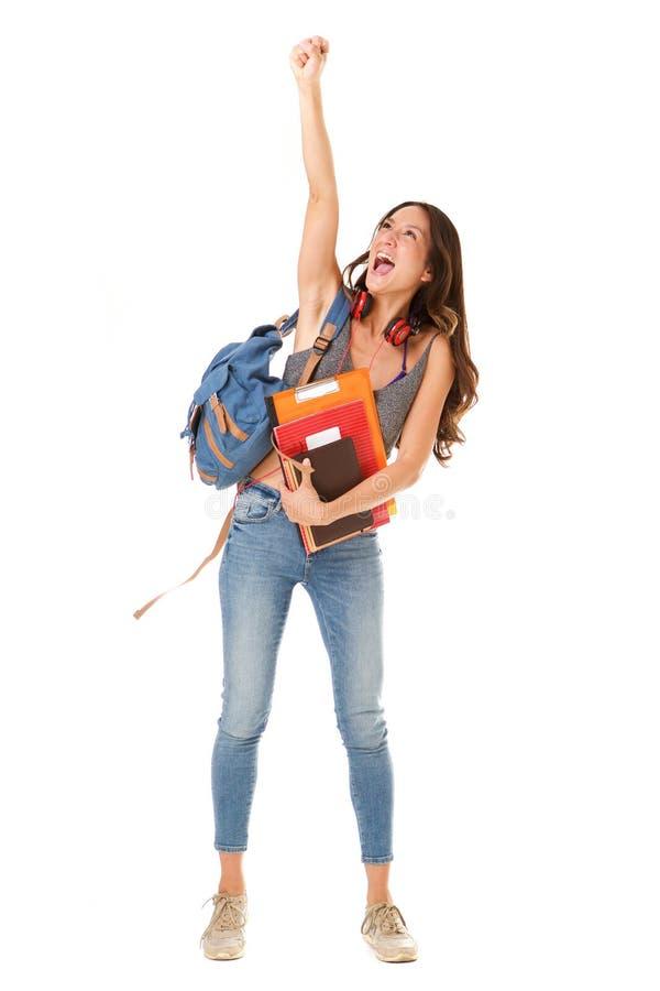 反对被隔绝的白色背景的快乐的亚裔女性大学生与被举的胳膊 免版税库存图片