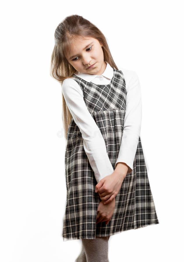 反对被隔绝的背景的逗人喜爱的害羞的女小学生 免版税图库摄影