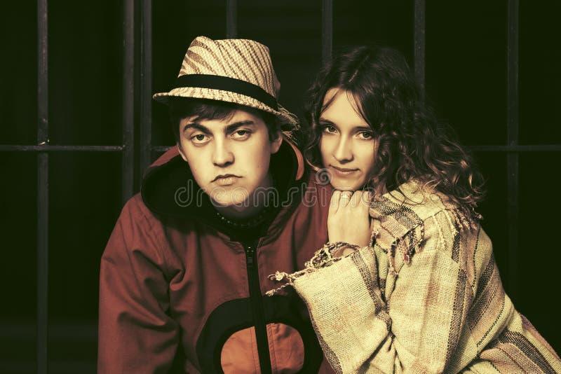 反对铁篱芭的年轻时尚嬉皮夫妇 免版税库存照片