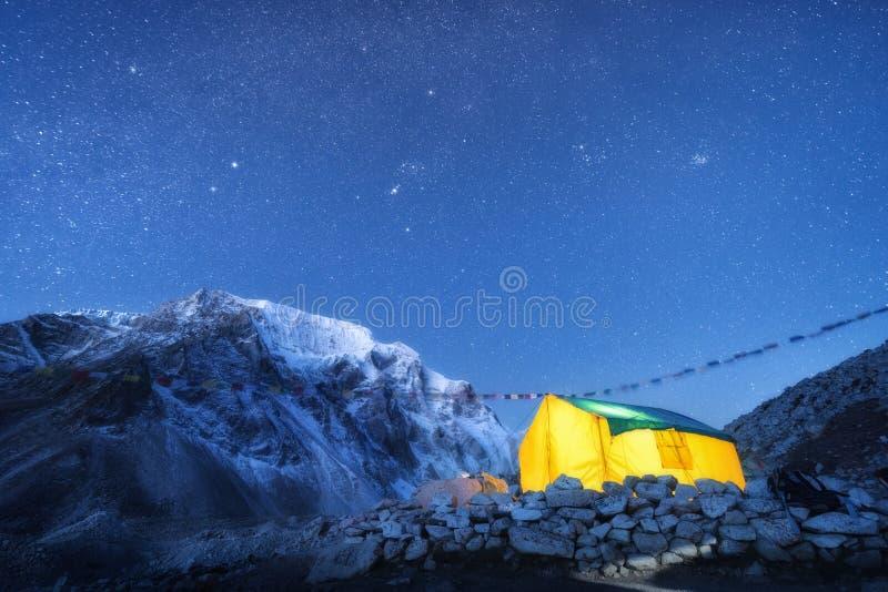 反对高岩石的黄色发光的帐篷与多雪的山峰和天空w 免版税库存图片