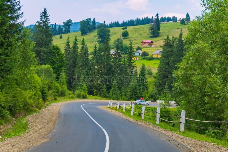 反对高绿色山小山背景的一个陡峭的弯曲道路  图库摄影