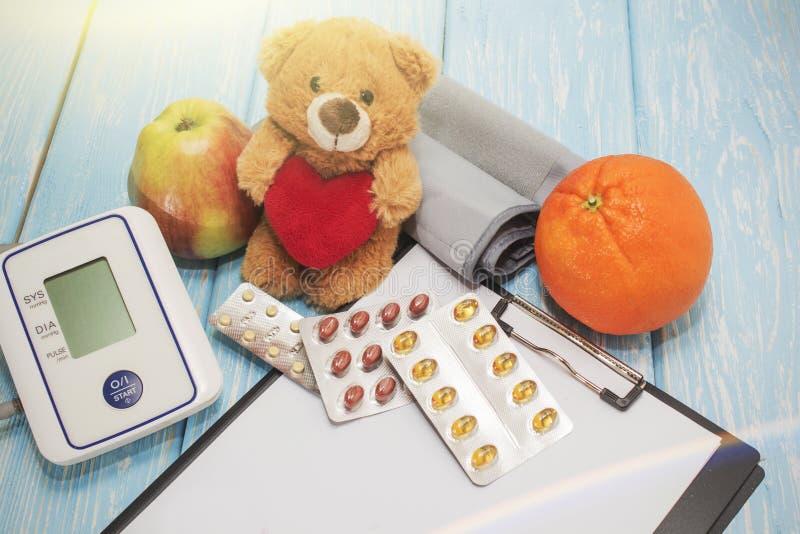 反对高血压的医疗药片,测量的血压的设备在背景中 免版税库存照片