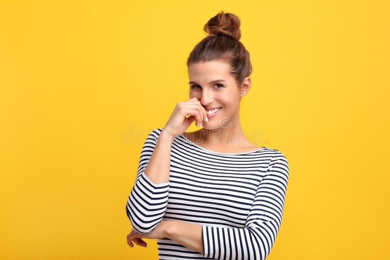 反对黄色墙壁背景的妇女 免版税库存图片