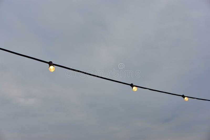 反对黑暗的天空的黄色发光的室外电灯泡 库存图片