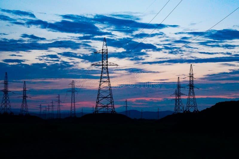 反对黑暗的日落天空的输电线 库存图片