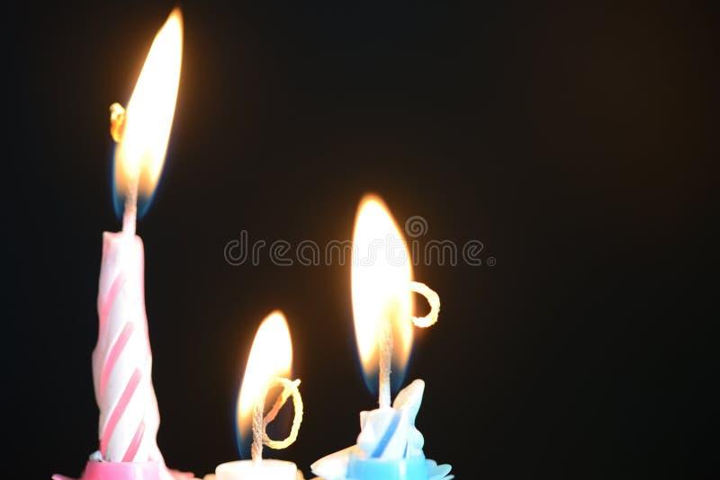 反对黑暗的背景的三个生日蜡烛 库存照片